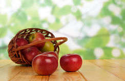 Wattled basket with the apples. On wooden table royalty free stock images