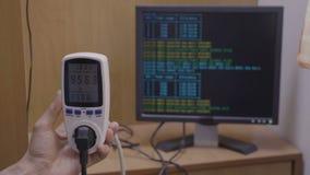 Wattmeter die op het tarief van het machtsgebruik van de installatie van de cryptocurrencymijnbouw en PC met cryptisch proces wij stock footage