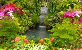 Watwerfall und Blumenbeete im Frühjahr mit üppigen Farben, Kanada Lizenzfreies Stockfoto