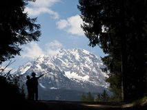 Watzmann, seen through the woods. Watzmann, Bavarian Alps, seen from the woods. Two silhouettes of kids point at the mountain. Taken from a walking path through Stock Image