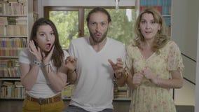 Wauw gelaatsuitdrukking van groep studentenvrienden die reactie in studieruimte hebben verrast - stock videobeelden