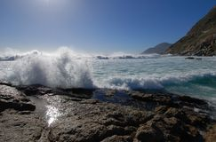 Wave action. Crisp waves of the Atlantic ocean explode onto the rocks at Cape Town Stock Photo