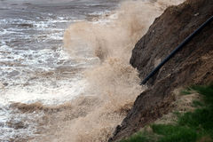 Wave action eroding clay cliffs. Stock Images