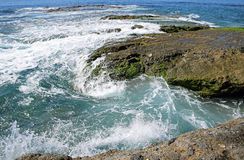 Wave action meets the rocky shoreline at Victoria Beach in Laguna Beach, California. Image shows wave action meeting the rocky shoreline at Victoria Beach in Stock Photo