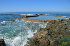 Wave action meets the rocky shoreline at Victoria Beach in Laguna Beach, California. Image shows wave action meeting the rocky shoreline at Victoria Beach in Stock Image