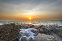 Wave attact rock and sun. Cloud Royalty Free Stock Photo