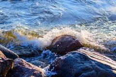 Wave avvolge la pietra enorme alla riva di mare fotografia stock