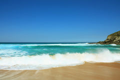 Wave on the beach in Suances, Spain. Beautiful beach in summer with clean sand and blue sky in Suances, Spain royalty free stock image