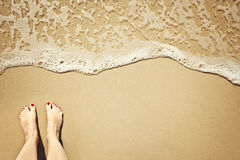 Wave on beach, feet to the left Stock Images
