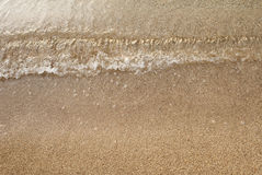Wave on beach. Small wave on surface of golden sandy beach stock photography