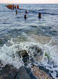 Wave beatting against the rock on sea shore. Waves, rocks and poles Stock Image