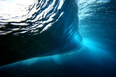 Wave From Behind. Wave explodes underwater. A look from underneath Stock Image