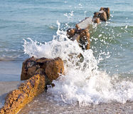 Wave breaker in the ocean. Stone wave breaker on the shore of the ocean with a wave breaking on it, Madeira Beach, Florida, USA Stock Photo