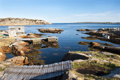 Wave Breakers. Newfoundland Coast showing Wharf and Shed among Rugged bedrock, and Fishermen in Small Boat Stock Photos
