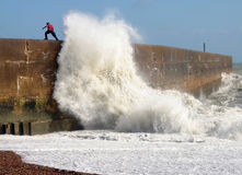 Wave breaking. A large wave crashing into pier with young lad playing chicken Royalty Free Stock Photography