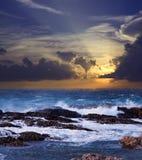 Wave breaking against coast rock. Sea wave breaking against coast rock in sunset time Stock Photography