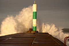 Wave breaking against lighthouse D stock photos