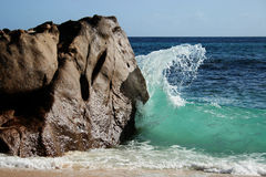 Wave breaking against rock. On the island of Seychelles royalty free stock image
