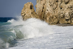 Wave breaking against rocks Royalty Free Stock Images