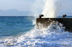 Wave breaking against stone mooring Royalty Free Stock Photos