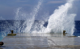 Wave breaking against stone mooring Stock Images