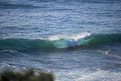 Wave breaking with a blue green calm sea at the back. royalty free stock photos