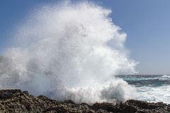 Wave breaking at the coast. A storm sends sunlit waves splashing on the Mediterranean coast of Gozo Malta Stock Photography