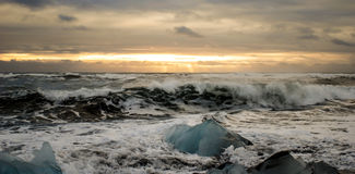 Wave breaking on ice. Stormy sunset in Iceland, Vik Royalty Free Stock Photography
