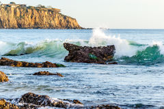 Wave breaking on an offshore rock on the California Coast. Beautiful blue-green wave breaking on a rock just offshore on the California coast, sending sea spray Royalty Free Stock Photography