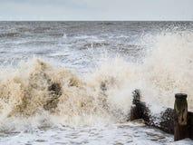 A wave breaking over a wooden groyne, water breaker. Stock Photo