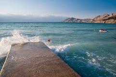 Wave breaking on pier on beach at Baska - Krk -Croatia Stock Photos