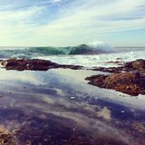 Wave breaking and rock pool stock images