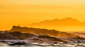 Wave breaking on the rocks at sunset. Royalty Free Stock Photo