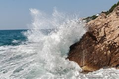 Breaking wave. Wave breaking on rocky coastline. Photo taken on near Bar city (Montenegro, Europe Stock Photos