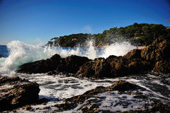 Wave breaking at the rocky shore. Shoreline in southern France, Cote d'Azur, Ile des Hyeres, Port du Niel stock image