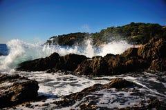 Wave breaking at the rocky shore. Shoreline in southern France, Cote d'Azur, Ile des Hyeres, Port du Niel Stock Image