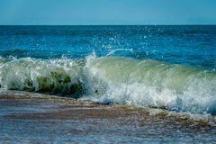 Wave breaking on a sandy shoreline Royalty Free Stock Image