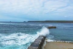 Wave breaking on Sennen cove fishing harbor breakwater Stock Image
