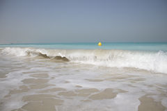 Wave breaking in turquoise waters on a white sand beach Royalty Free Stock Images