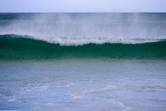 Wave breaking, with wind spray Stock Images