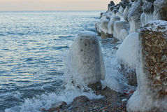 The wave breaks against an icy stone Royalty Free Stock Photography