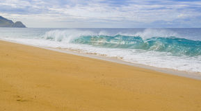 Wave breaks on Pacific Ocean beach. Clear, blue, waves break on the shore of a Pacific coast beach in Todos Santos, Baja California Sur Mexico Stock Images