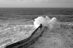 Wave breaks on Portreath pier, Cornwall UK. Royalty Free Stock Images