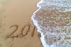 Wave cancelling the 2018 written on the sand. The 2018 written on the sand while the wave is cancelling the 8 symbolising the coming end of the year stock images