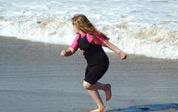 Wave chase. Young girl on beach Royalty Free Stock Photo