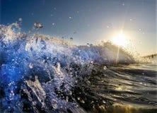 Wave che rompe sole dietro fotografie stock libere da diritti