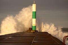 Wave che si rompe contro il faro D Fotografie Stock