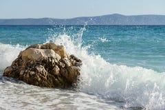 Wave che spruzza sulla pietra della roccia Immagine Stock