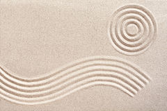 Wave and circles in a Japanese zen garden. Undulating flowing wave pattern and concentric circles raked in the sand in a traditional Japanese zen garden for Royalty Free Stock Photography