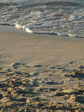 Wave coming into shore on sandy beach Stock Photo
